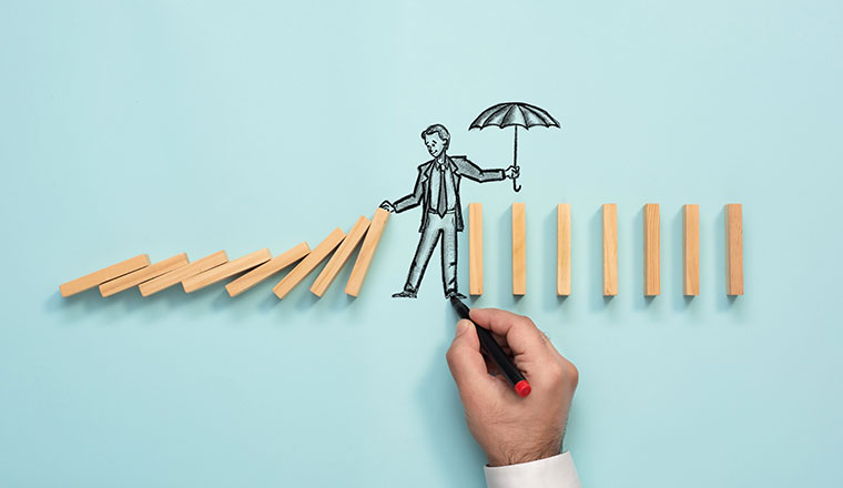 A picture of someone holding an umbrella over wooden blocks