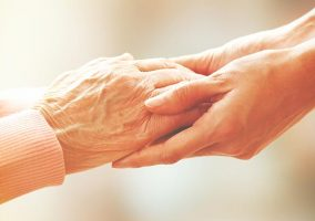 A photo of someone holding an elderly persons hands