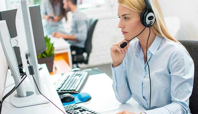 A picture of a contact centre agent looking at a desktop