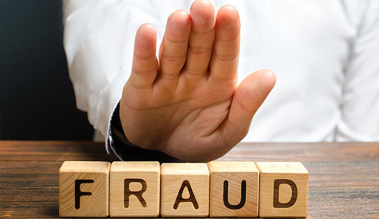 A picture of the word Fraud on wooden dice