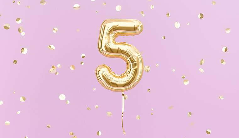 A photo of a gold balloon in the shape of the number 5