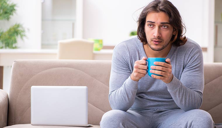 A person drinking tea whilst sat on a sofa next to a laptop