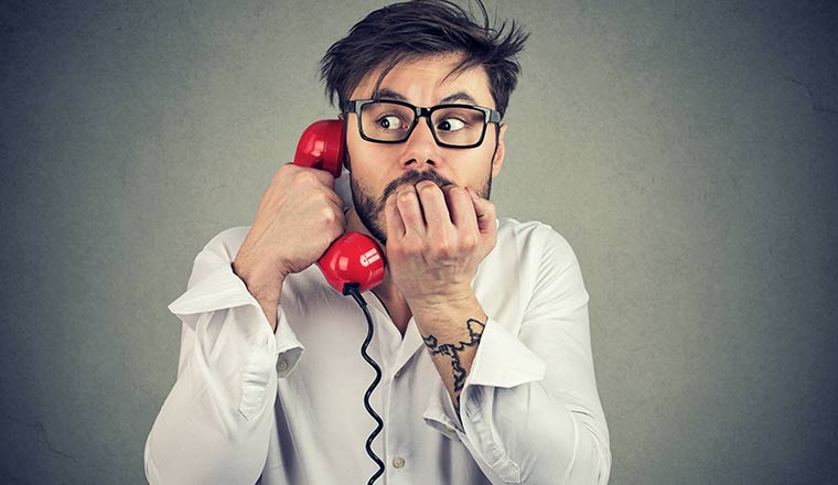 A picture of a person looking nervous on the telephone