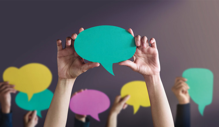 A picture of people holding up speech bubbles