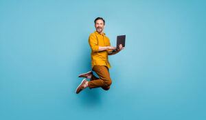 A photo of someone jumping in the air with a laptop