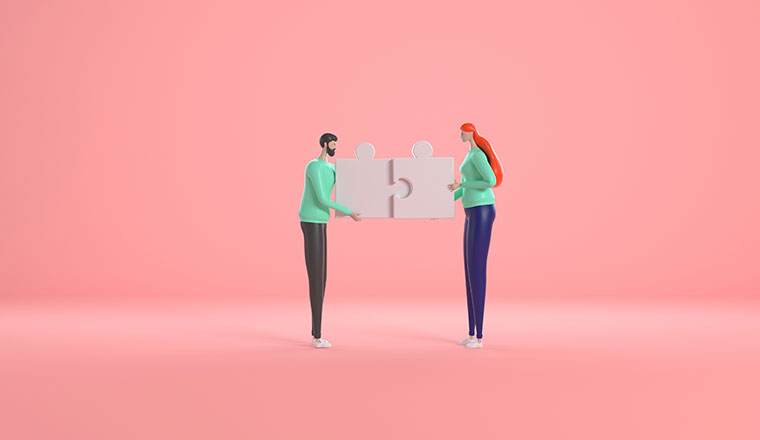 A photo of two people connecting puzzle pieces