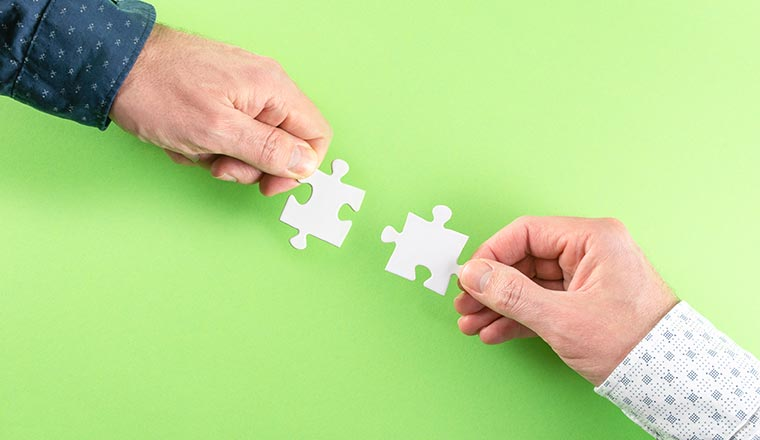 A photo of two people connecting puzzel pieces