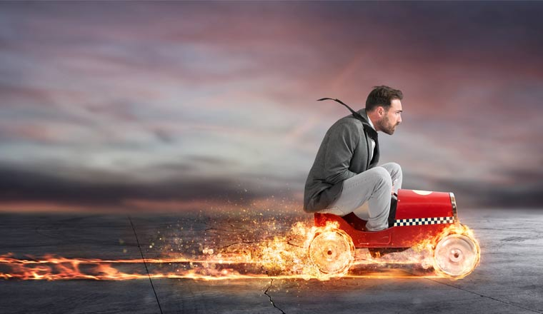 A picture of a business man driving a toy car with tyre on fire