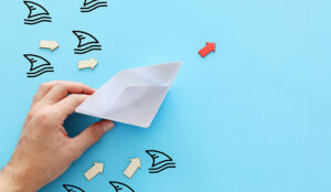 A picture of a paper boat avoiding shark fins