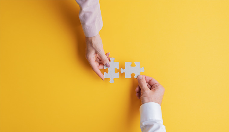A picture of hands joining two matching puzzle pieces