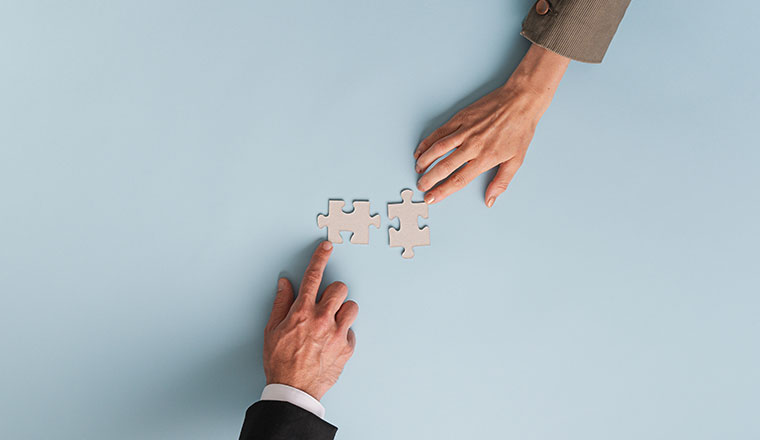 A photo of two busiess hands connecting puzzle pieces