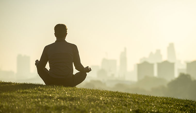 A picture of someone meditating outside