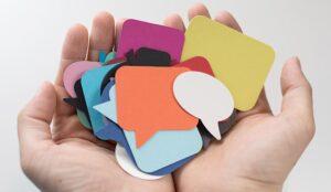 A photo of multi-colour speech bubbles in hands