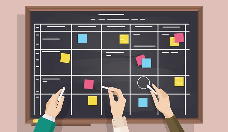 A picture of a scheduling with post-it notes board with