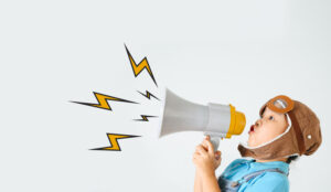 A picture of a child shouting down a megaphone