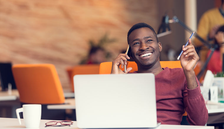A picture of a happy agent on the phone sat at a desk