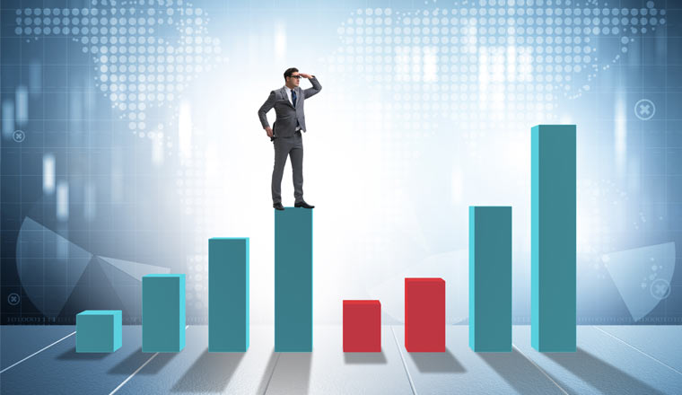 A picture of a person stood on a bar chart and looking to the future