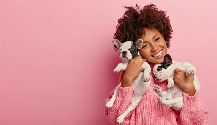 A picture of a lady holding two puppies