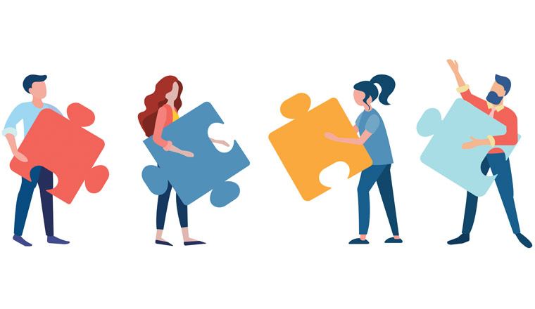 A picture of workers holding puzzle pieces