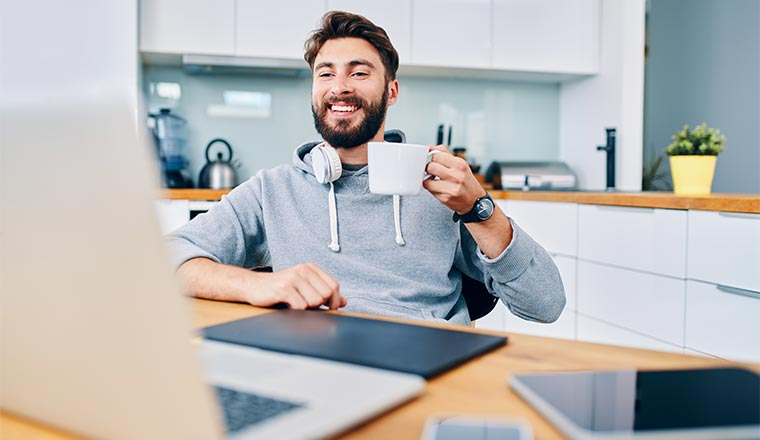 A photo of a remote worker raising their coffee cup