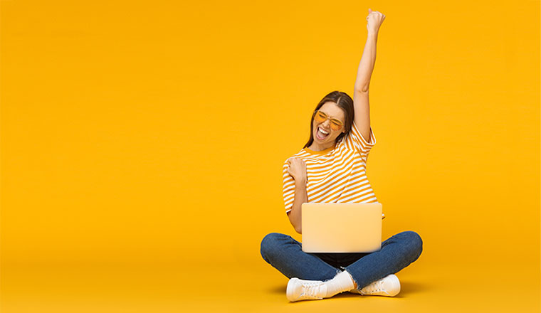 A photo of someone celebrating at their computer
