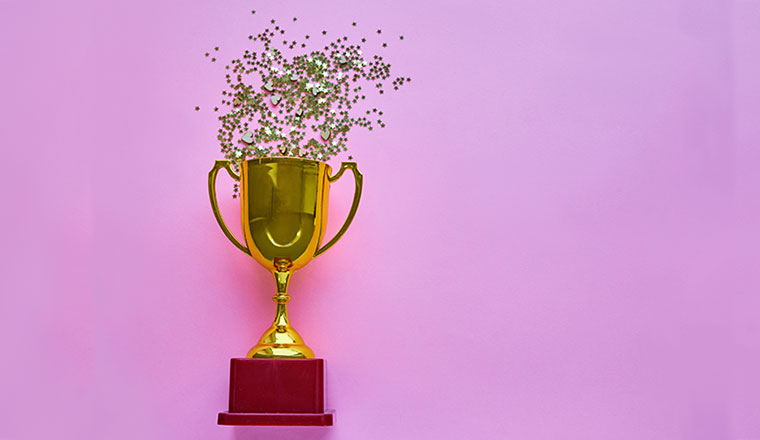 A photo of a trophy with gold confetti