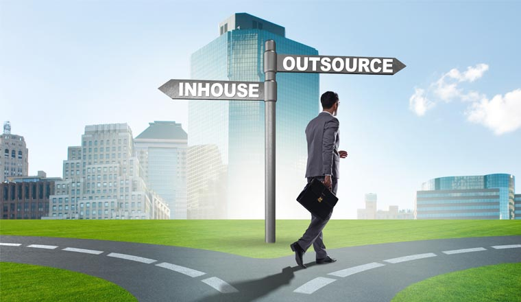 A picture of an agent at a crossroads deciding between outsourcing and inhouse