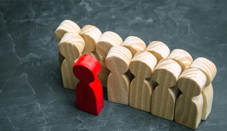A picture of wooden figures with a chosen red figure