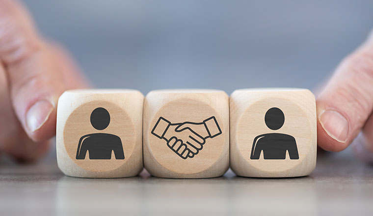 A photo of a handshake with blocks