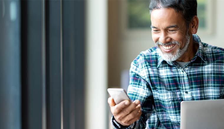 A picture of a happy customer holding a mobile phone