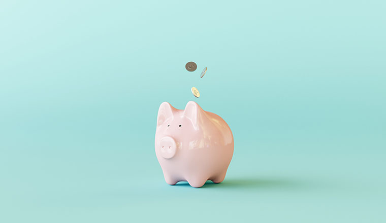 A picture of money going into a piggy bank