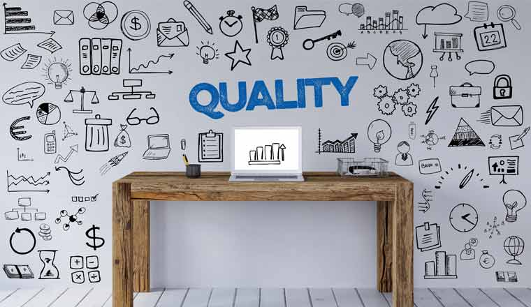 A picture of the word quality doodles on a wall behind a desk with laptop