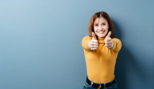 A picture of a person holding up her thumbs