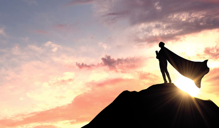 silhouette of lady standing on top of mountain with cape on