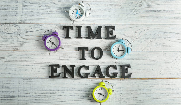 A picture of Clocks and phrase Time to Engage on wooden background