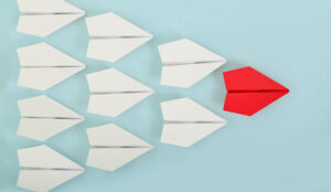 A picture of a red paper boat leading a group of boats