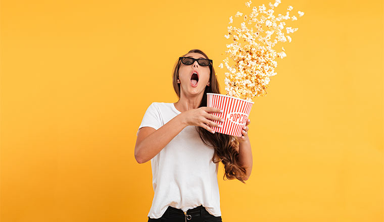 A photo of someone in shock, eating popcorn