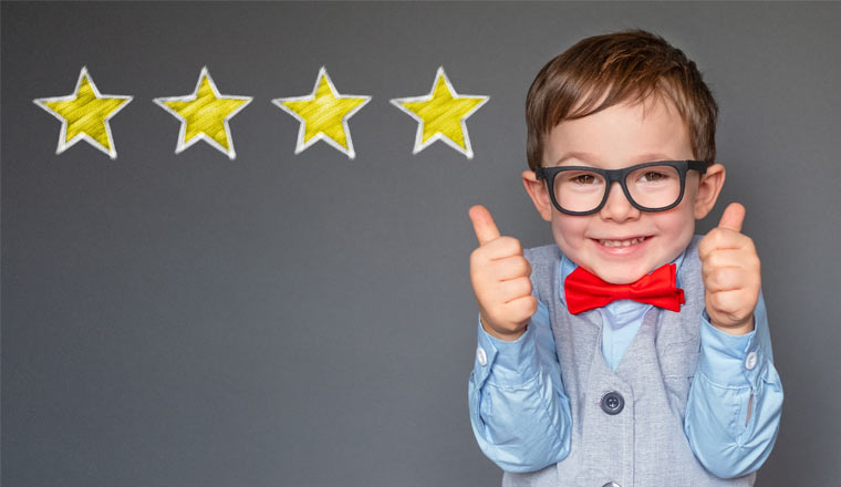 A picture of a young boy holding up his thumbs with four stars