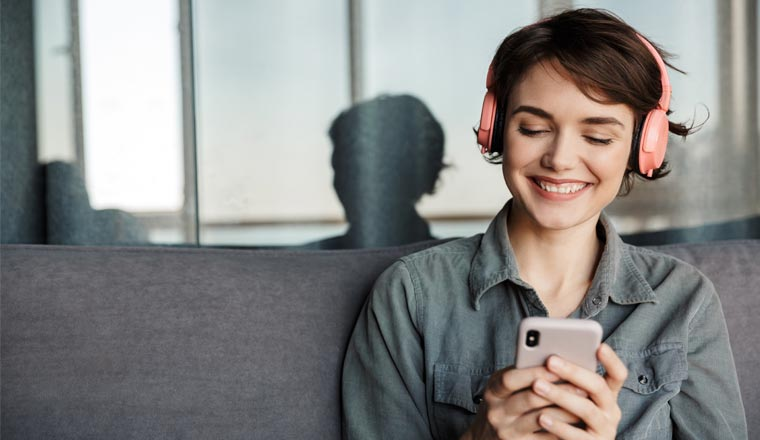 A picture of a lady wearing headphones and listening to a podcast on mobile