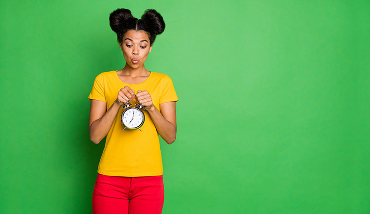 A photo of someone posing with a clock