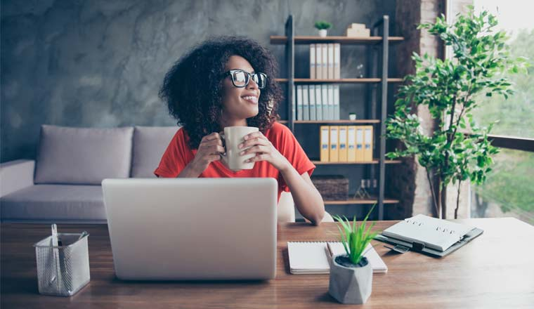 A picture of a remote worker sat at desk with a cup of coffee