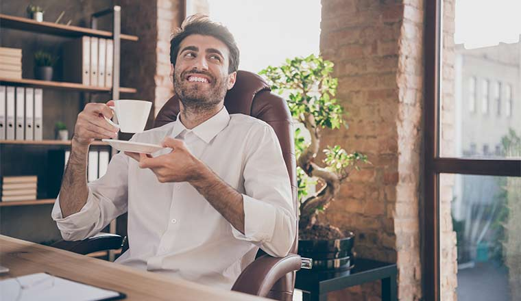 A picture of a man sipping tea in an office