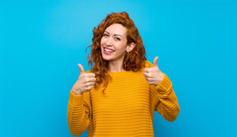 A picture of a lady holding her thumbs up