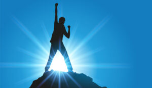A picture of a person stood on top of a rock celebrating with hands in the air