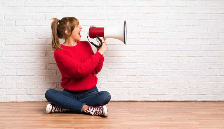A picture of a lady shouting through a megaphone