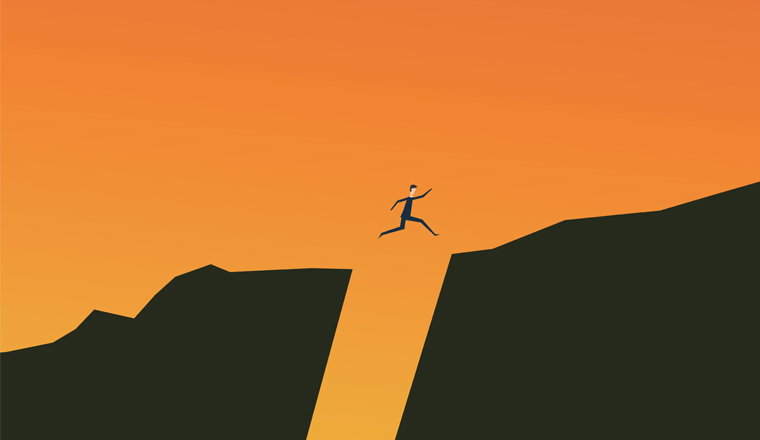 A picture of a person jumping over a gap between rocks