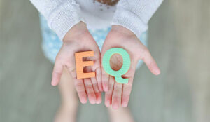 """A photo of someone holding the letters """"EQ"""""""