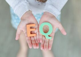 "A photo of someone holding the letters ""EQ"""