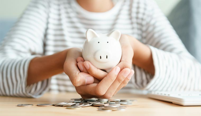 A picture of a person holding a piggy bank