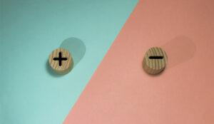 A picture of a plus and minus on wooden buttons